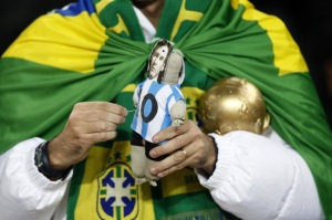 A Brazil fan in the stands with a voodoo doll of Lionel Messi and a replica of the world cup trophy