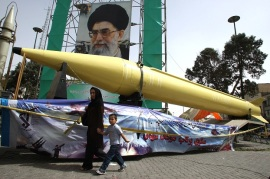 """An Iranian woman and her son walk past Shahab-2 (L) and Shahab-3 missiles on display in front of a large portrait of Iran's Supreme Leader Ayatollah Ali Khamenei in a square in south Tehran on September 28, 2008. Iran marked """"Sacred Defence Week"""", which commemorates Iran's bloody eight-year war with Iraq. The United States has recently deployed an anti-missile radar in Israel that is mainly to warn of incoming Iranian ballistic missiles, Israeli state radio reported today. AFP PHOTO/ATTA (Newscom TagID: afpphotosthree008755) [Photo via Newscom]"""