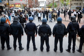 Police stand in a line near protestors after a rally for Freddie Gray, Saturday, April 25, 2015, in Baltimore. Gray died from spinal injuries about a week after he was arrested and transported in a police van. (AP Photo/Patrick Semansky)