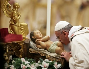 Pope Francis kisses a statue of baby Jesus as he celebrates the Christmas Eve Mass in St. Peter's Basilica at the Vatican, Tuesday, Dec. 24, 2013. (AP Photo/Gregorio Borgia)