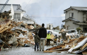 A father and child who lost their home stand in front of debris in Sendai, northern Japan Saturday, March 12, 2011 after Japan's biggest recorded earthquake slammed into its eastern coast Friday. (AP Photo/Kyodo News) MANDATORY CREDIT, NO LICENSING ALLOWED IN CHINA, HONG KONG, JAPAN, SOUTH KOREA AND FRANCE