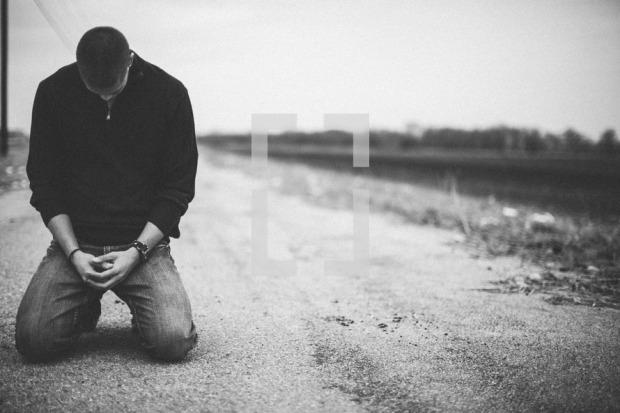 lightstock-60129-man-kneeling-in-prayer-in-the-middle-of-a-rural-road.jpg