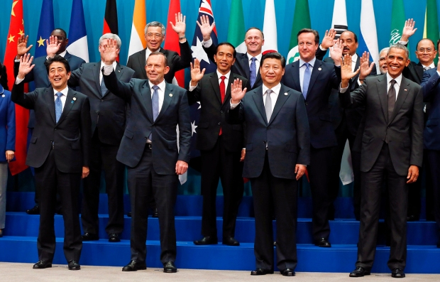 G20 leaders and partner groups wave during a group photo at the annual G20 summit in Brisbane